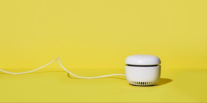 Das Notruf- und Kommunikationssystem CARU auf gelben Grund. Das CARU ist mit einem Kabel verbunden.