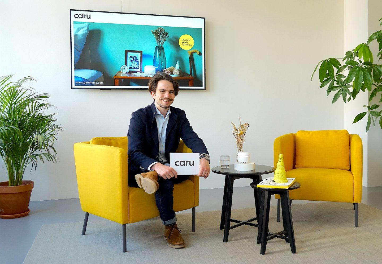 Nico Dudli sitz auf einem gelben Sessel, im Rahmen der digitalen Altenpflege. Er hält Moderartionskarten in der Hand und lächelt.