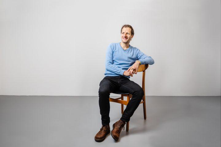 Co-Founder und Co-CEO Thomas Helbling sitzend auf einem Holzstuhl vor einer weissen Wand. Er trägt einen blauen Pullover, schawrze Jeans und braune Schuhe.
