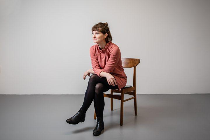 Anina Segat sitz auf einem Stuhl aus Holz. SIe schaut nachdenklich in die Ferne, dabei trägt sie ein lachsfarbenes Kleid.