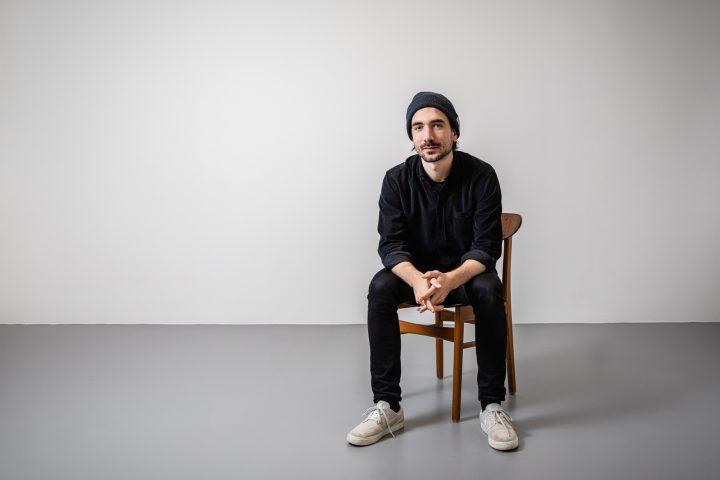 Designer Renè vom Studio Porto sitz entspannt auf einem Stuhl. er ist komplett in schwarz gekleidet.