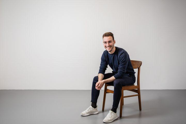 Simon Sommer auf sitzend auf einem Stuhl. Er grinst in die Kamera und trägt eine Brille.