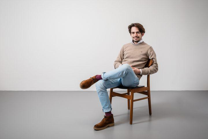 Nico Dudli sitzt auf einem Stuhl. Ein Bein auf dem anderen. Er trägt eine Jeans.