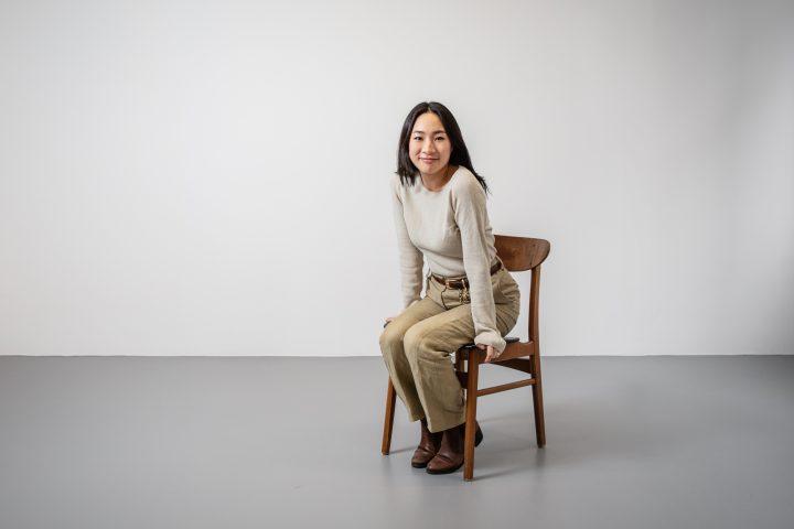 Mia Kang sitzend auf einem Holzstuhl vor einer weissen Wand. Sie schaut direkt in die Kamera. Sie trägt einen beige Pullover und hat dunkles Haar.