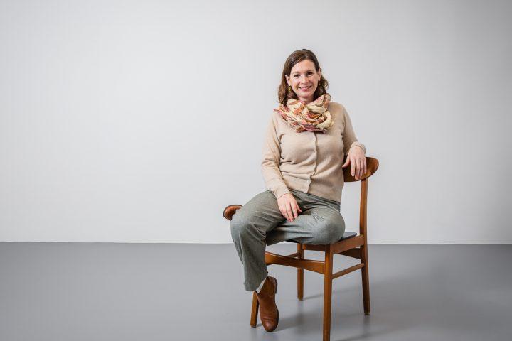 Co-CEO und Co-Founder Susanne Dröscher sitz auf einem Designerstuhl. Sie hat die Beine übereinandergelegt und schaut freundlich in die Kamera.