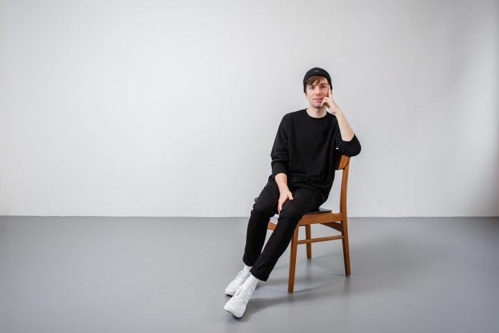 Christian sitz auf dem Stuhl mit einer Hand im Gesicht. Er trägt aussschliesslich schwarz.