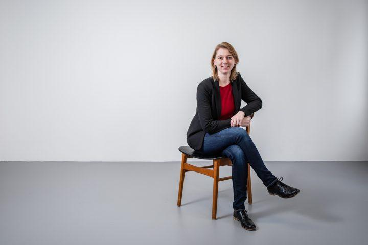 Susanne Müller sitz quer auf einem Holzstuhl. Sie lächelt sympatisch in die Kamera.