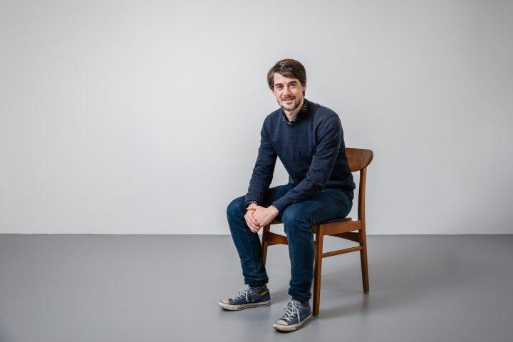 Andreas Husi sitzend auf einem Holzstuhl vor einer weissen Wand.