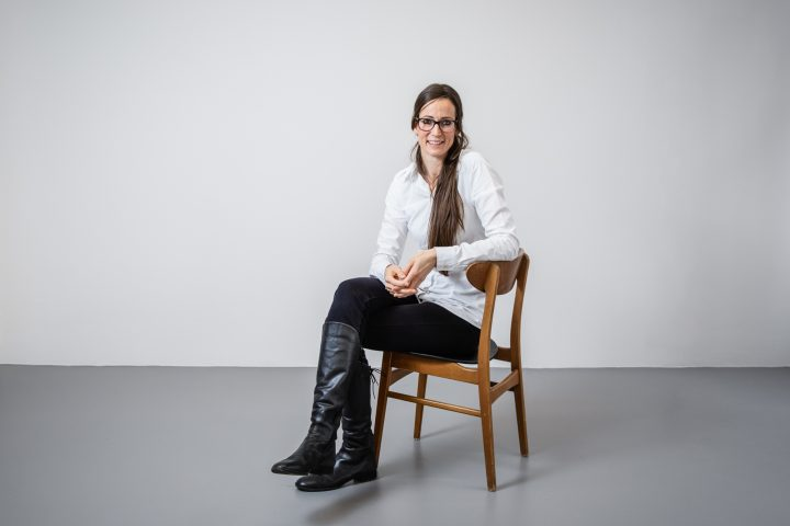 Katherina Rodharth sitzt auf einem Stuhl. Sie hat schwarze Stiefel und brauens Haar.