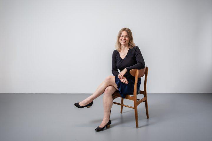 Franziska Dammeier sitz auf einem Stuhl. Sie trägt einen Rock offenes Haar und eine Brille. Sie lächlet.