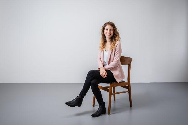 Rochelle Aberer sitz auf einem Stuhl. Sie hat Locken und schwarze Stiefel.
